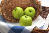 Three green apples in the brown wicker basket — Stock Photo