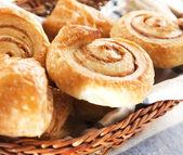 Cinnamon danish bun in the basket on textile background — Stock Photo