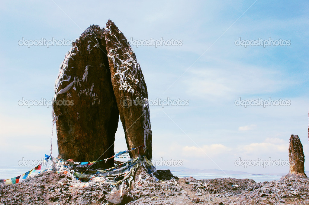 Landscape of huge rocks wrapped with colorful prayer flags at a lakeside in Tibet — Zdjęcie stockowe #10954427
