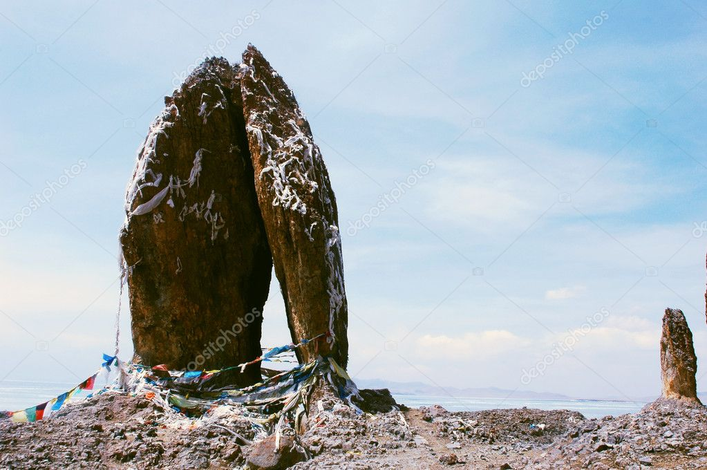 Landscape of huge rocks wrapped with colorful prayer flags at a lakeside in Tibet — Stock Photo #10954427