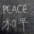 Peace - word written on a blackboard with a Chinese translation — Stock Photo