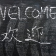 Welcome - word written on a blackboard with a Chinese version — Stock Photo