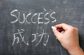 Success - word written on a blackboard with a Chinese translation — Stock Photo