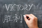 Victory - word written on a blackboard with a Chinese translation — Stock Photo