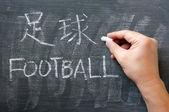 Fútbol - palabra escrita en una pizarra con una versión en chino — Foto de Stock