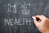 Wealth - word written on a blackboard with a Chinese version — Stock Photo