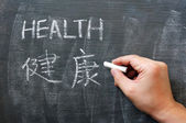 Health - word written on a blackboard with a Chinese version — Stock Photo