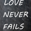 Love Never Fails written on a smudged chalkboard — Stock Photo