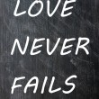 Love Never Fails written on smudged chalkboard — Stock Photo #11215550