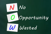 Acronym of NOW - No Opportunity Wasted on a chalkboard — Стоковое фото