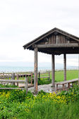 Wooden pavilion and fence in the grassland — Stock Photo
