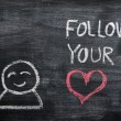 "Speech bubble with a cartoon figure and the phrase ""Follow your heart"" drawn on a blackboard background — Stock Photo"