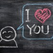 Speech bubble with a cartoon figure, saying I love you drawn on a blackboard background — 图库照片