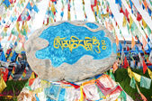 Tibetan prayer flags and mani rock — Stock Photo