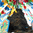 Stock Photo: Tibetprayer flags and mani rocks