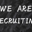 Concept of we are recruiting written on smudged blackboard background - Stock Photo