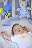 Baby sleeping peacefully in her crib — Stock Photo