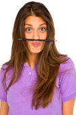 Teenage girl balancing pencil on her lip — Stock Photo