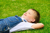 4 years old child lying on the grass. — Stock Photo