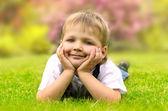 Little boy lying on a green grass — Stock Photo