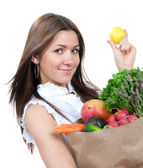 Woman holding a paper shopping bag full of groceries — Stock Photo