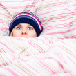 Scared woman hiding in duvet — Stock Photo