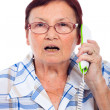 Shocked senior woman on the phone — Stock Photo