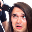 Unhappy man being shaved with hair trimmer — Stok fotoğraf