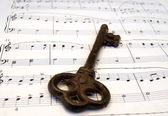Old key and a score — Stok fotoğraf