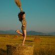 Happy, young woman jumping on hay stack — Stock Photo #11510323