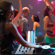 Woman dj entertaining crowd in night club - Stock Photo