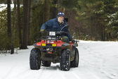 Senior riding ATV quad on the snow — Foto de Stock