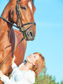 Young beautiful red girl with her horse in field — Stock Photo