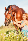 Pretty women with her horse in meadow — Stock Photo