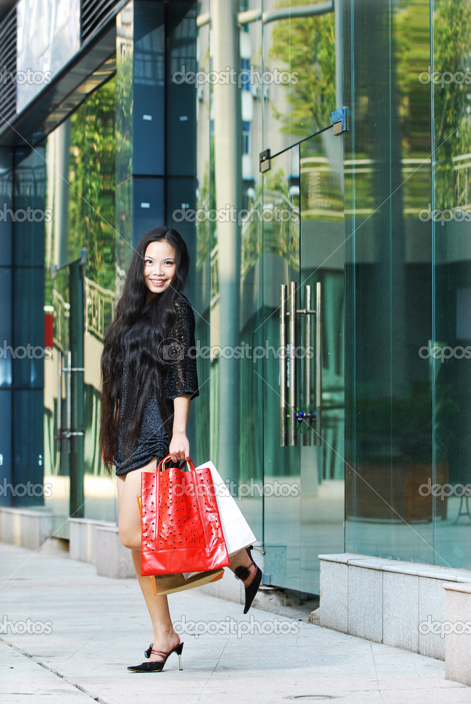 Shopping smiling asian woman holding bags   Stock Photo #11234671