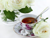 Cup of tea and white roses — Stock Photo