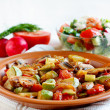 Roasted vegetables on rustic plate. Salad with fresh vegetables in background — Stock Photo #10770877