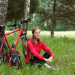 Woman cyclist relaxing among the green of nature — Foto de Stock