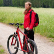 Woman cyclist on a bicycle walk on the green nature - Stock Photo