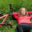 Woman cyclist relaxes lying among the green grass — Stock Photo