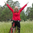 Excited woman cyclist standing on a nature with hands outstretched — Stockfoto