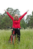 Excited woman cyclist standing on a nature with hands outstretched — Stock Photo