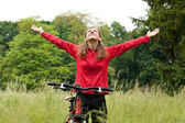 Excited woman cyclist with hands outstretched — Stock Photo