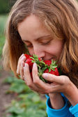 Young woman with red fresh strawberries in hands — Stock Photo
