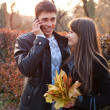 Happy couple in autumn outdoors. Man talking on mobile phone — Stockfoto