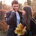 couple heureux à l'automne à l'extérieur. homme parle sur téléphone mobile — Photo