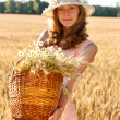 Young woman with basket full of ripe spikelets of wheat in the field - Stock Photo