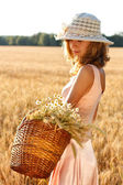Beautiful woman with basket full of ripe spikelets of wheat in the field — Stock Photo
