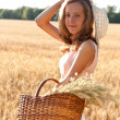 Young woman with basket full of ears wheat and hat — Stock Photo