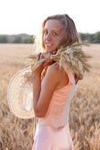 Happy woman with ears wheat and a hat in her hands — Stock Photo